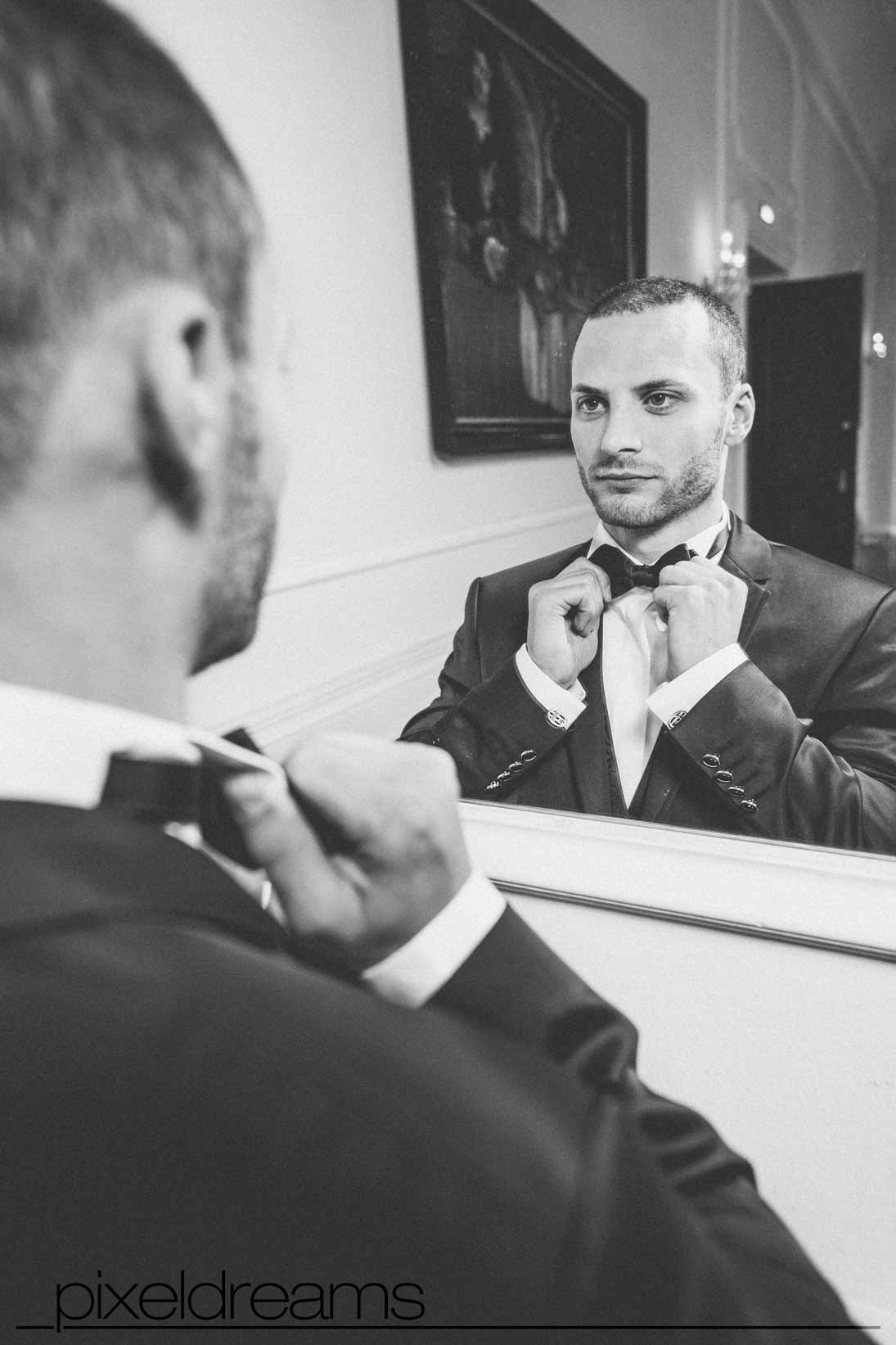 bräutigam richtet sich die fliege vor dem spiegel im schloss dyck