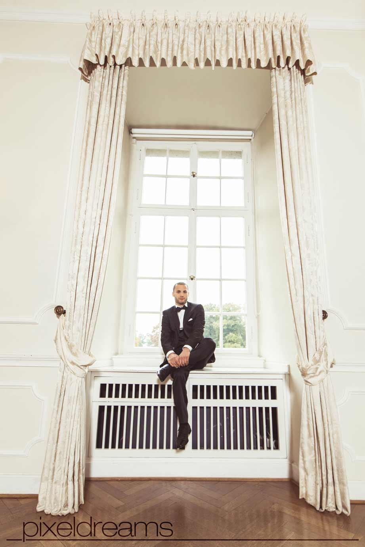bräutigam sitzt cooler pose im schloss am fenster - pose cool anzug schuhe bräutigam