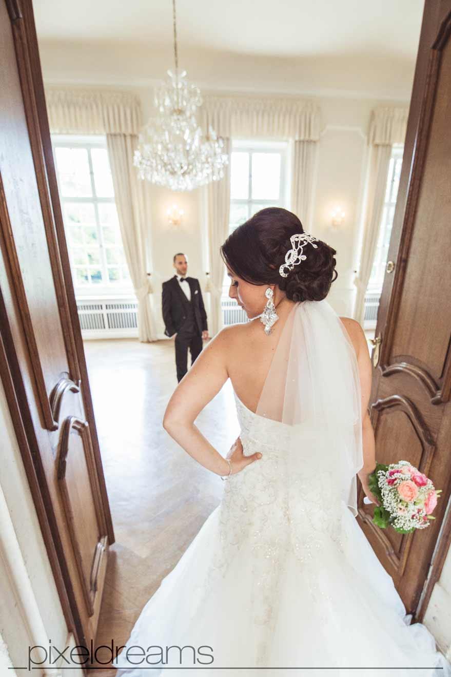 braut steht mit ihrem brautstrauß am eingang vor dem saal im schloss dyck während der bräutigam unter dem kronleuchter wartet