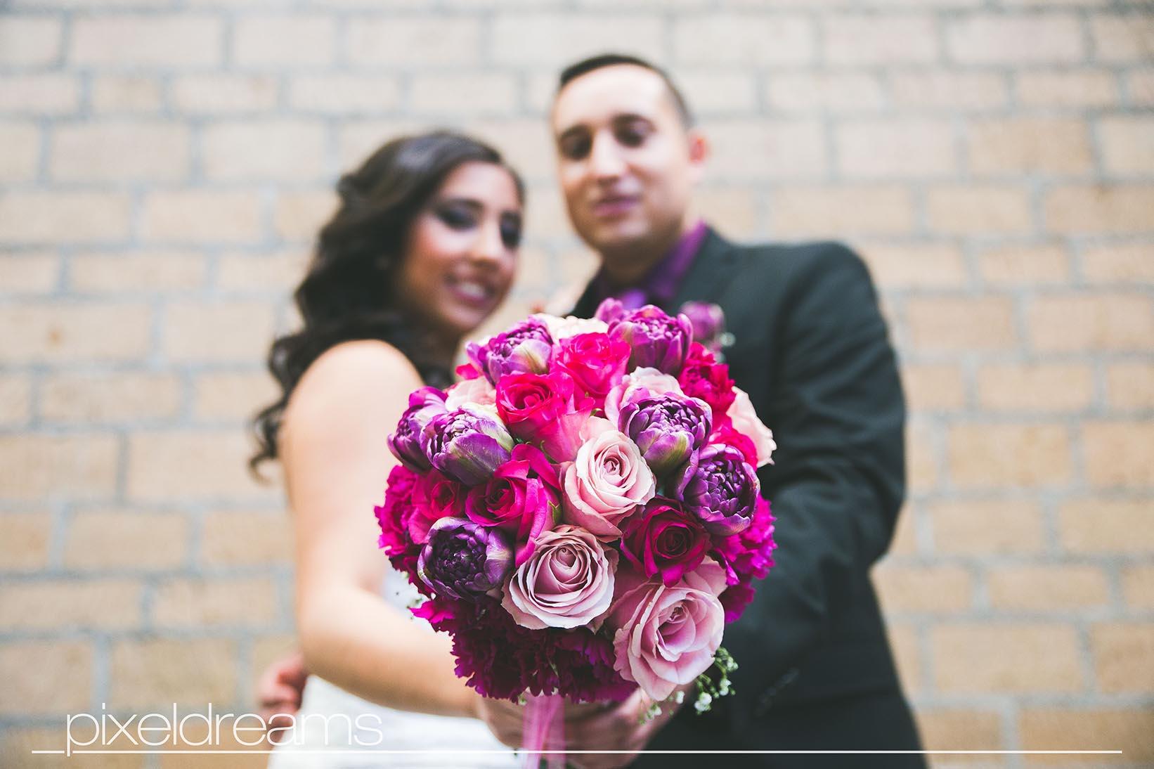 Brautpaar hält Brautstrauß gegen die Kamera, das paar ist in der tiefenunschärfe und der Blumenstrauß im Fokus