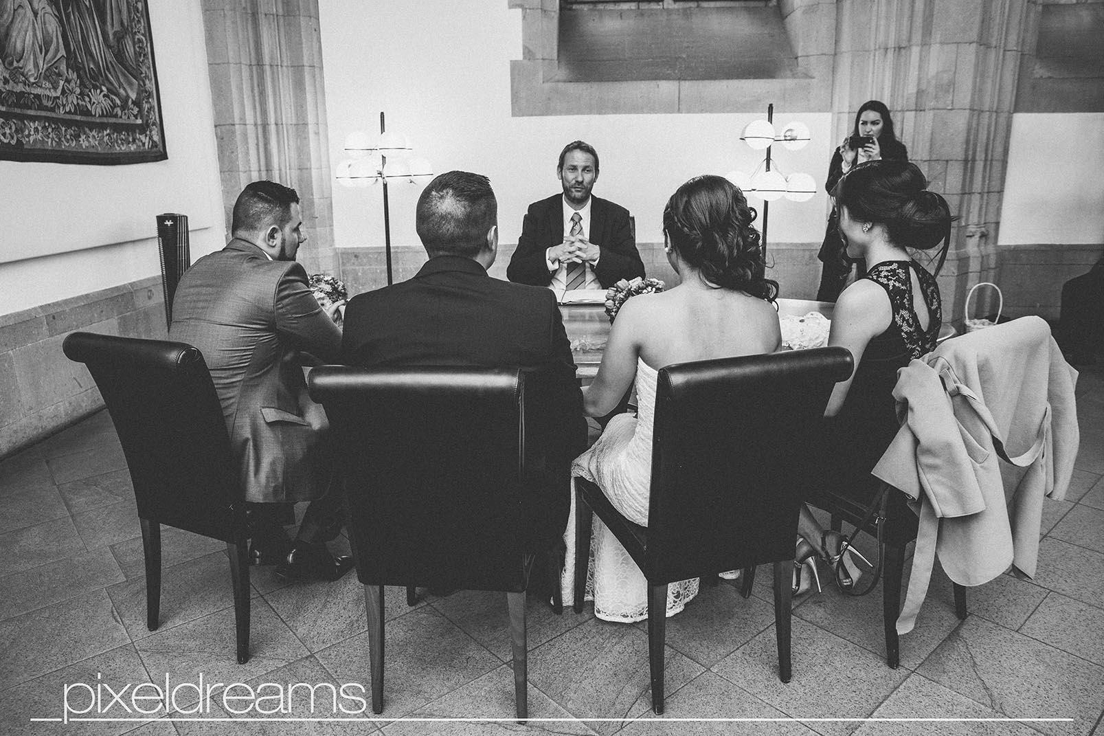 Braut Bräutigam und Trauzeugen sitzen beimm Standesamt vor dem Standesbeamten