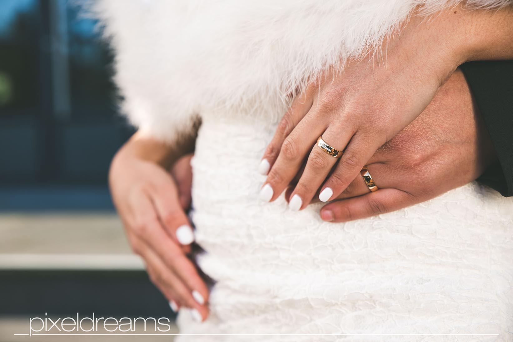 Detailaufnahme von den Trauringen / Eheringenund dem Brautkleid - hochzeitsfotos