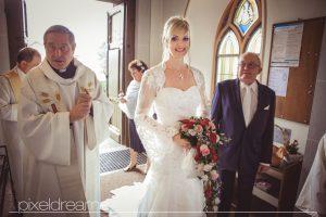 Die Braut betritt die St. Antonius Kirche in Swisttal. Der Bräutigam wartet sehnsüchtig auf seine Liebste. Hochzeitsfotos in Swisstal durch Pixeldreams.