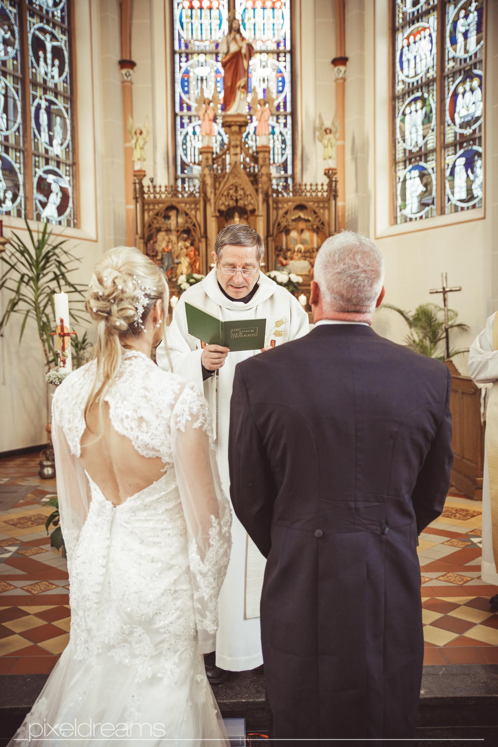 Hochzeitsfoto während Pastor Trauung der Braut und des Bräutigams vollzieht. Jesus Figur und Altar im Hintergrund am Altar der St. Antoniuskirche in Swisttal.