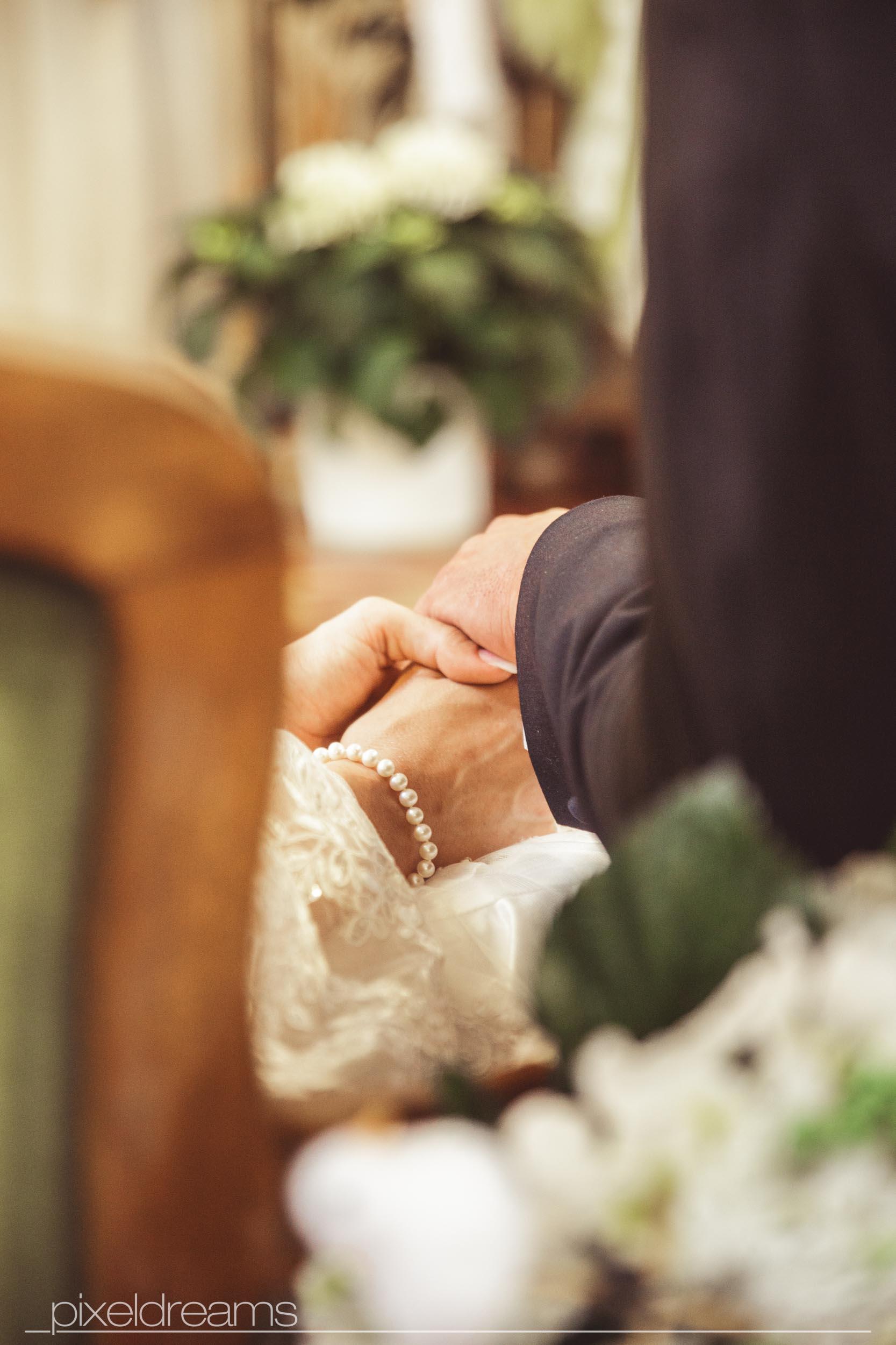 Detailaufnahme des Händchenhaltenden Brautpaares. Der Altar der St. Antoniuskirche Swisttal ist in der Tiefenunschärfe zu sehen.
