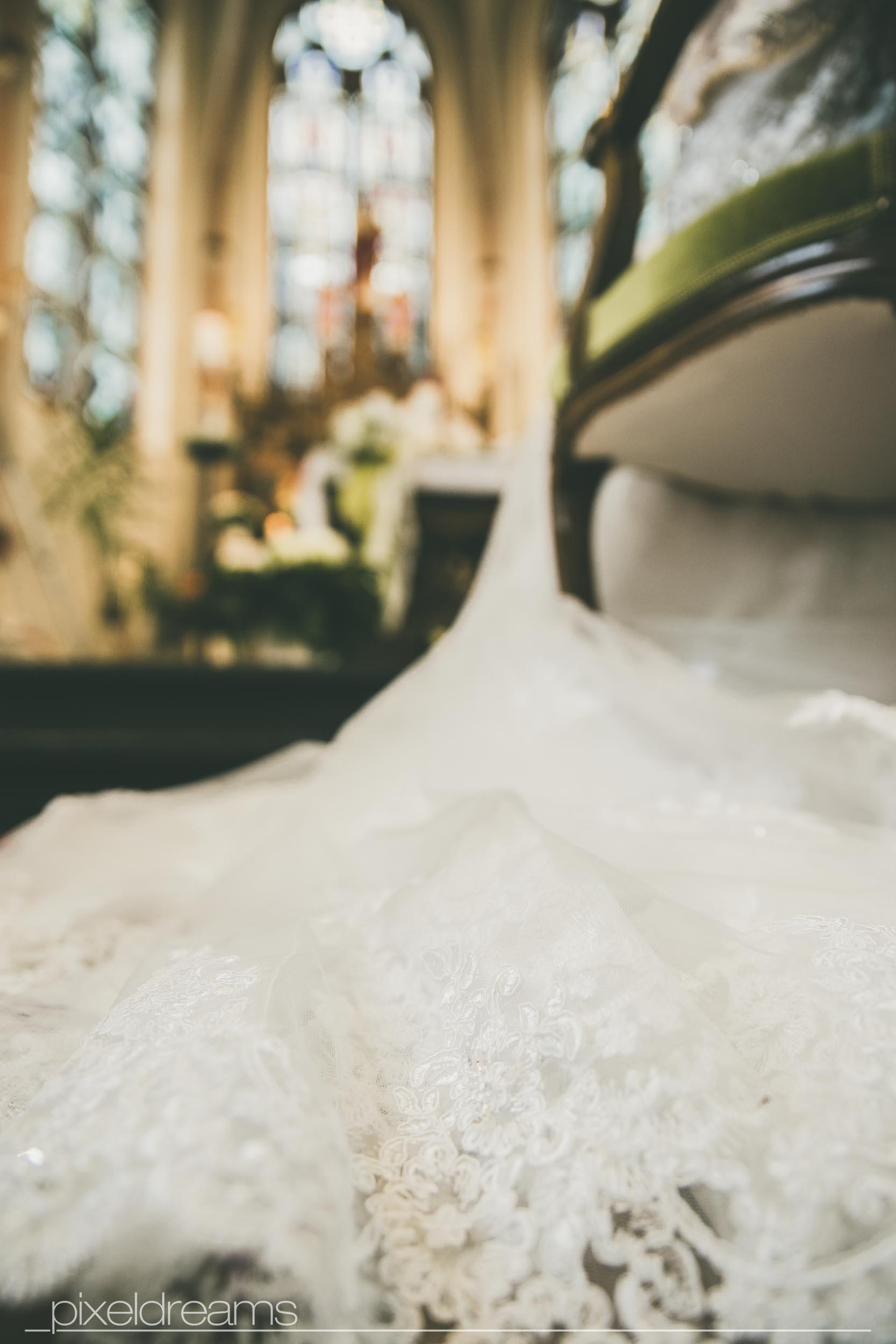 Hochzeitsfoto aus der Froschperspektive. Detailfoto des Brautkleides. Altar der St. Antonius Kirche in Swisttal in unscharfem Hintergrund zu sehen.