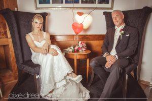 Braut und Bräutigam posen sitzend vor dem Hochzeitsfotografen für ihre Hochzeitsfotos.