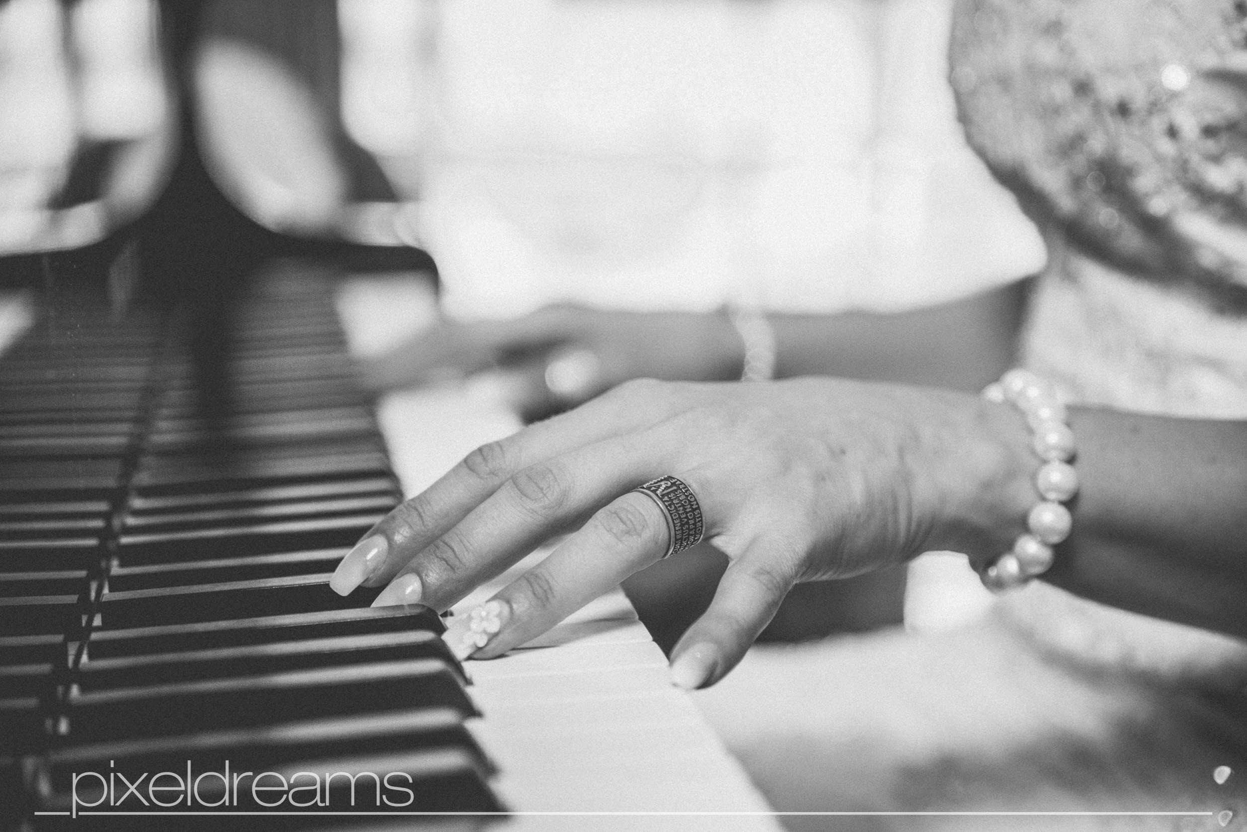 Braut spielt Klavier man sieht ihren Trauring, Hochzeitsfotograf macht Hochtzeitsfotos