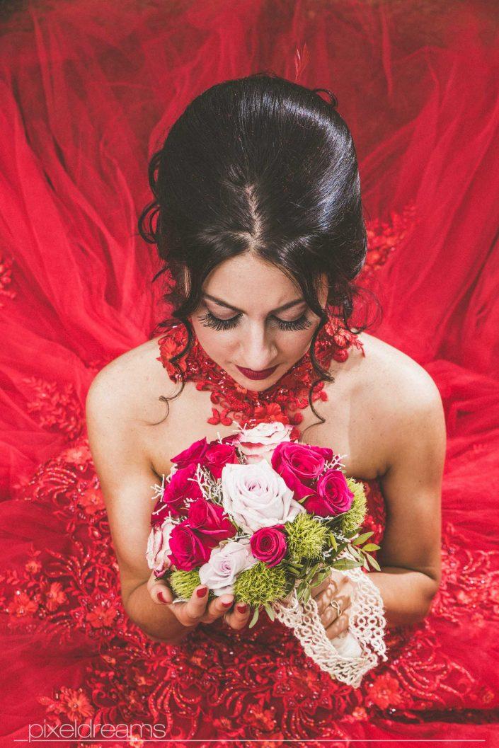 Henna Fotos, Kına Resimleri – Braut mit Blumenstrauß/ Brautstrauß im Hennakleid, rotem Ballkleid aus der Vogelperspektive fotografiert. Entfesselt geblitzt mit einer Softbox. Rotes Ballkleid kommt schön zur Geltung. Brautfrisur und Braut Make Up/ Abend Make Up kommen ebenfalls schön zur Geltung. Braut schaut verträumt auf ihr Brautstrauß. Henna Foto
