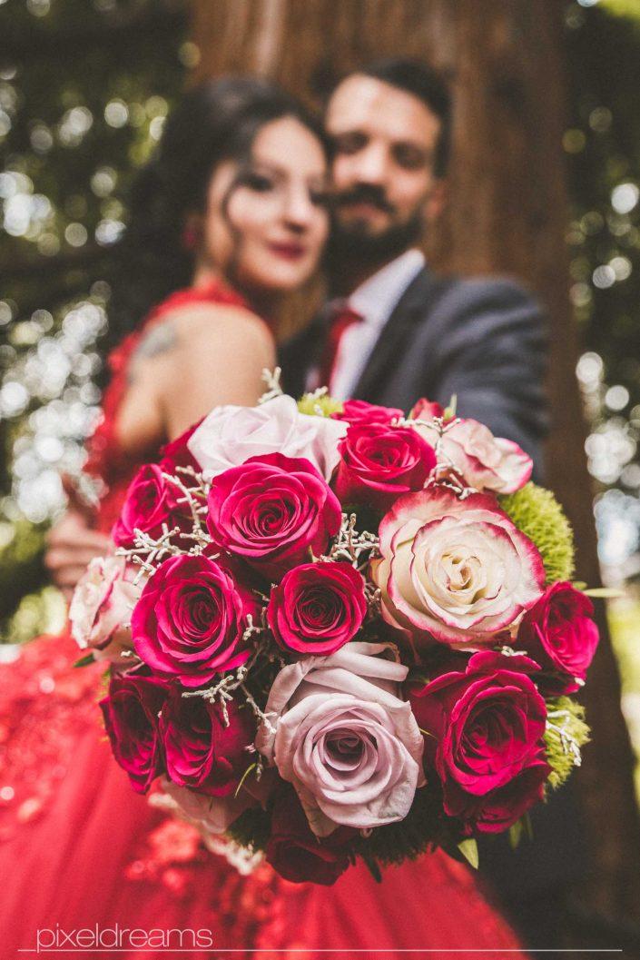 Henna Fotos, Kına Resimleri – Brautstrauß wird vom Brautpaar festgehalten und in die Kamera des Hochzeitsfotografen gehalten. Das Foto ist aus der Froschperspektive aufgenommen. Im Fokus steht der Brautstrauß während das Brautpaar in der Tiefenunschärfe posiert.