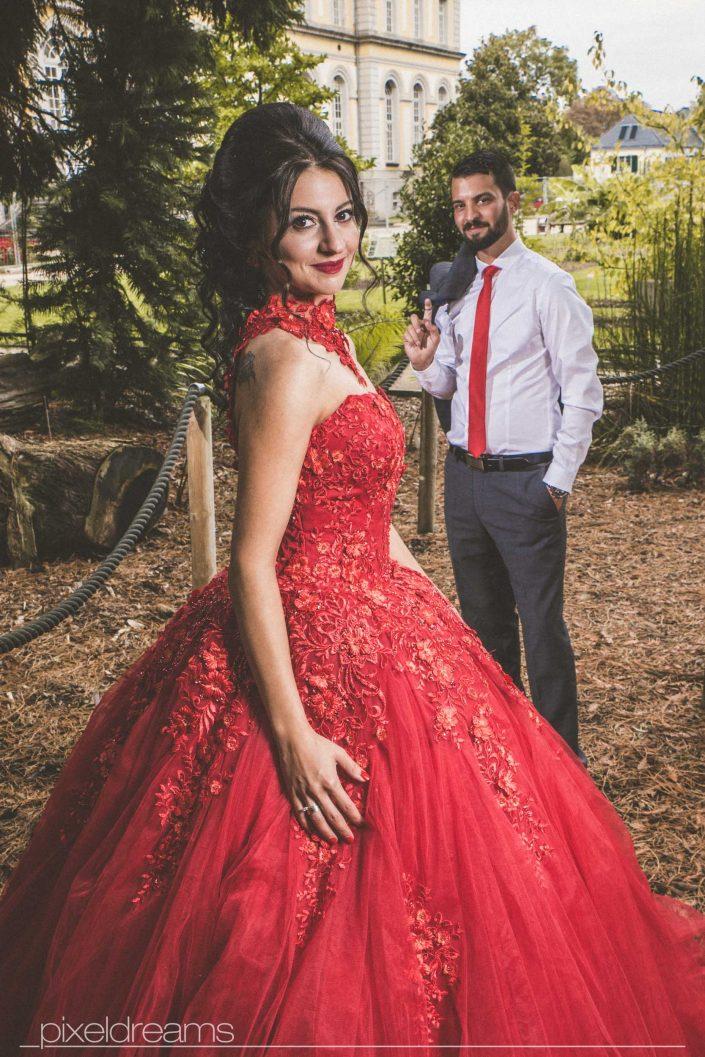 Henna Fotos, Kına Resimleri – Braut im wunderschonen Hennakleid Kına Elbise mit Bräutigam im Hintergrund; fotografiert im Botanischen Garten Bonn vom Hochzeitsfotografen. Henna Fotos