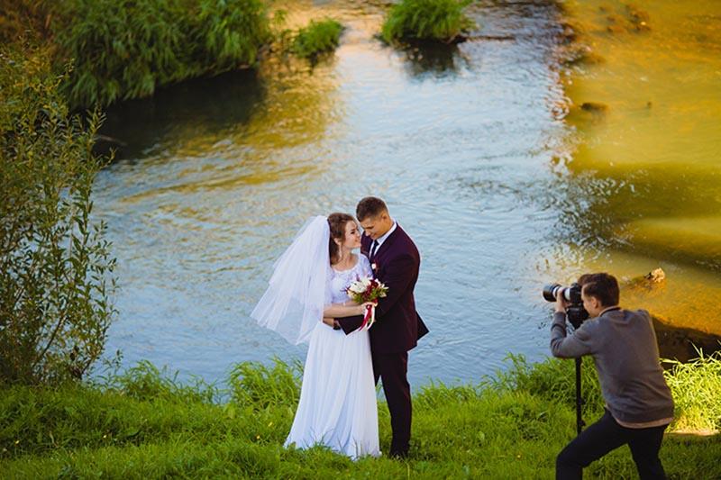 Hochzeitsvideograf filmt Brautpaar am Teich in Köln