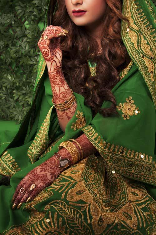 Braut mit bemalten händen und armen posiert im grünen sari