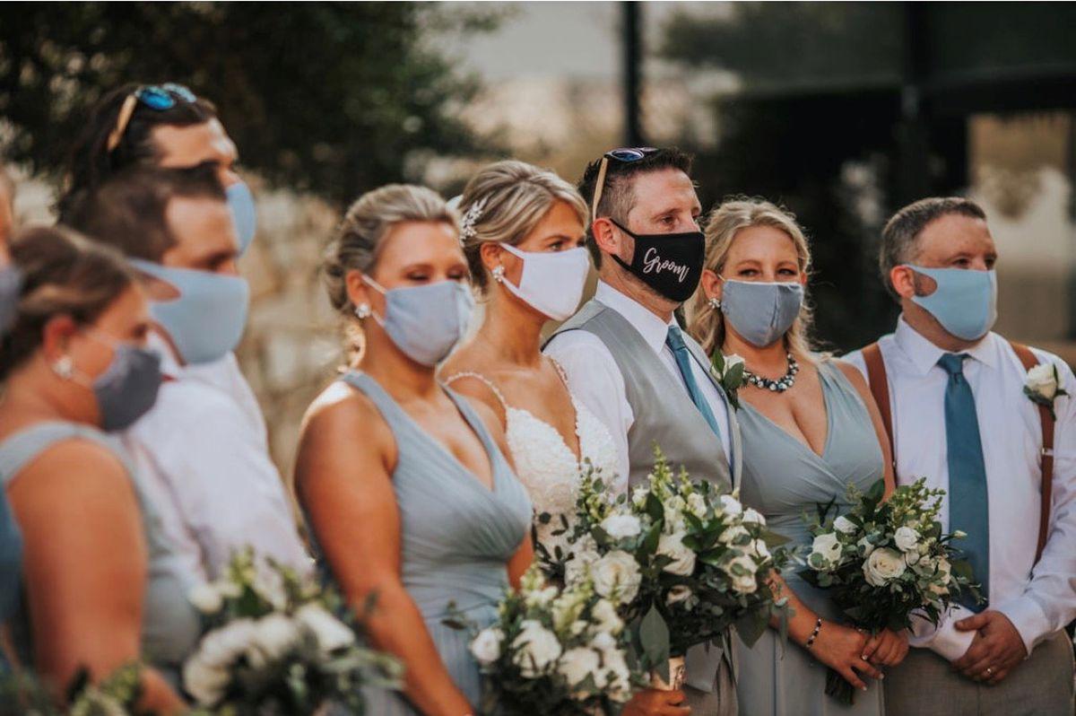 Brautpaar mit Brautjungfern und Best men stehen mit Corona Maske im Freien