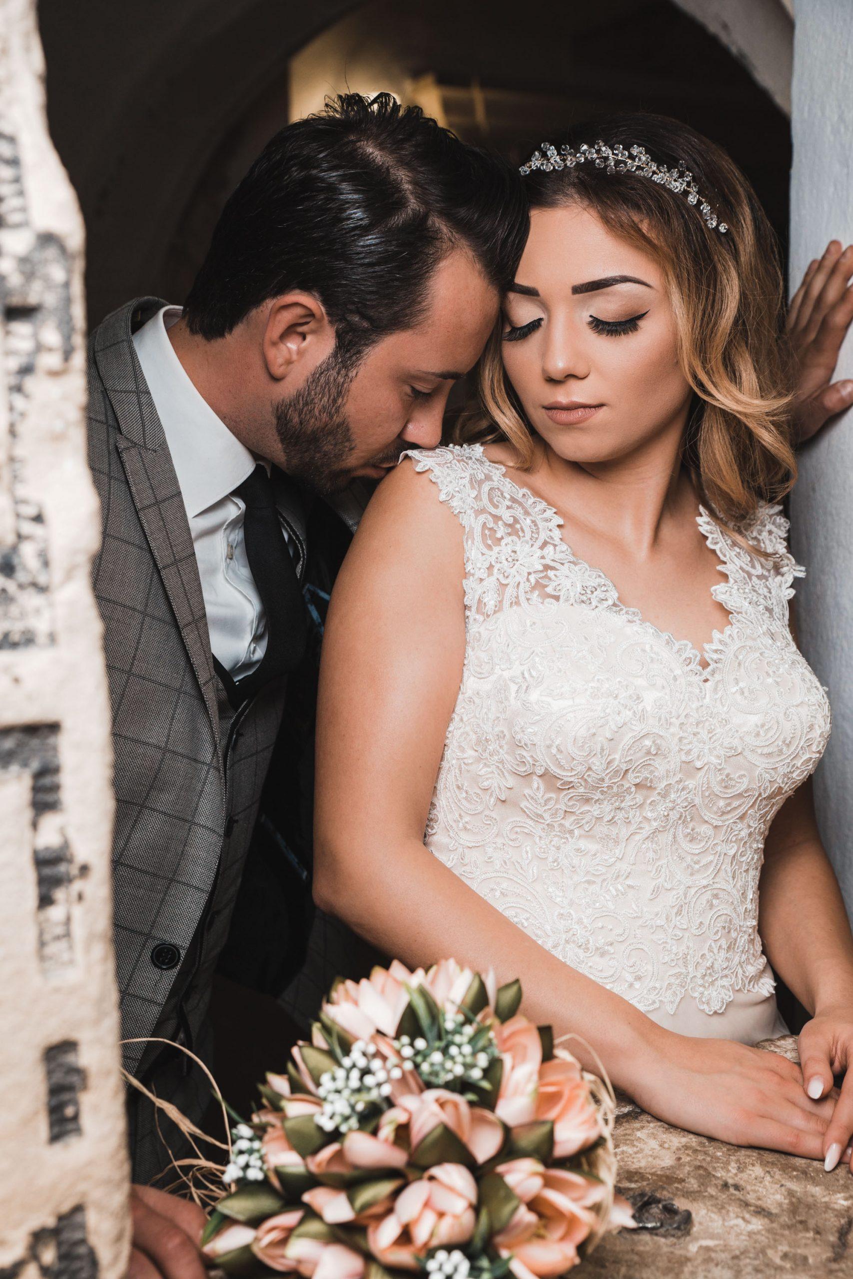 Hochzeitsbild eines türkischen Brautpaares. Türkischer Hochzeitsfotograf Fotografiert das Paar in einer sinnlichen Pose. Bräutigam küsst Braut auf die Schulter. Kreatives Hochzeitsfoto.