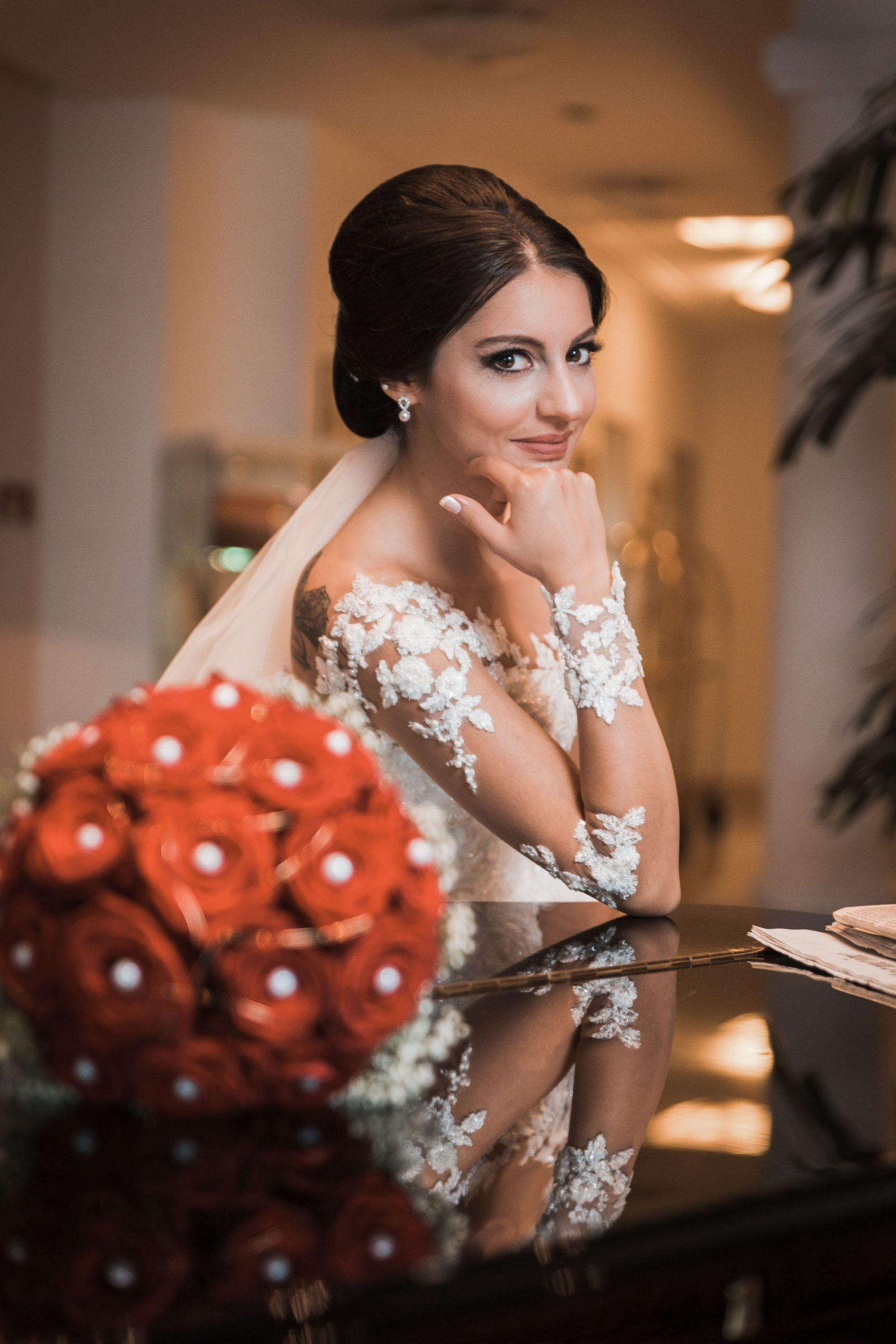Hochzeitsfoto einer türkischen Braut Mit rotem Rosestrauß Bouquet im Vordergrund. Braut schaut lächelnd und verlegen in die Kamera. Perfekte Brautfrisur und tolles perfektes Braut Mac ab. Sie posiert über einem Klavier.