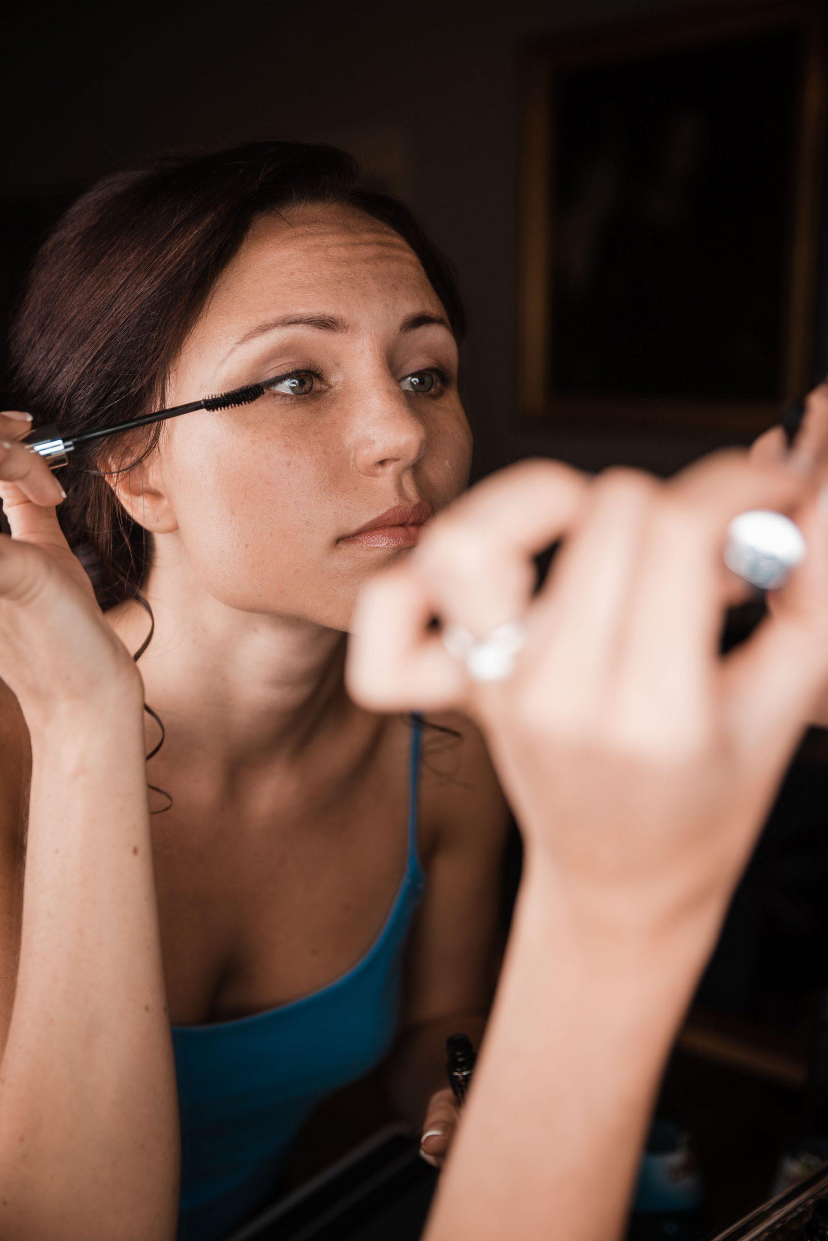 Hochzeitsfoto einer Braut beim Getting dressed. Braut legt selbst Hand an und tuscht ihre Wimpern. Natürliches Hochzeitsfoto vom Hochzeitstag.