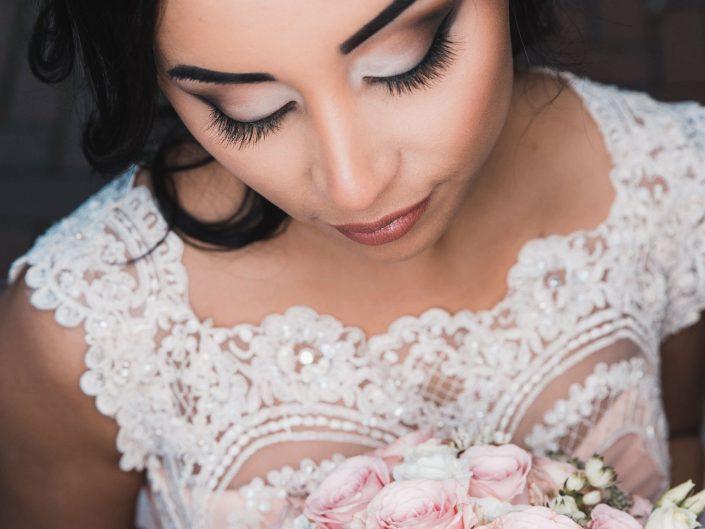 Hochzeitsbild einer schönen Braut mit perfektem Braut Styling und Brautfrisur. Hochzeitsfoto aus erhöhter Perspektive. Braut schaut verträumt auf ihren Brautstrauß.
