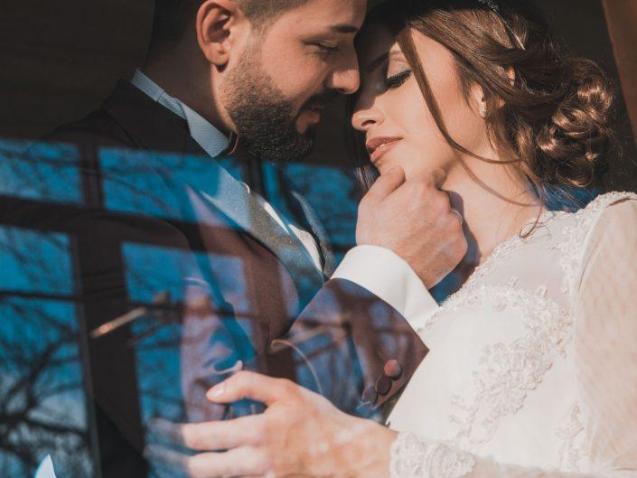 Hochzeitsbild vom Hochzeitsfotografen entstanden im Geschichtsmuseum Lüdenscheid. Brautpaar posiert sinnlich in einer alten Lokomotive. Fotograf betrachtet das Geschehen von außen. Das Fenster vom Zug ab Teil reflektiert. Kreatives Hochzeitsfoto.