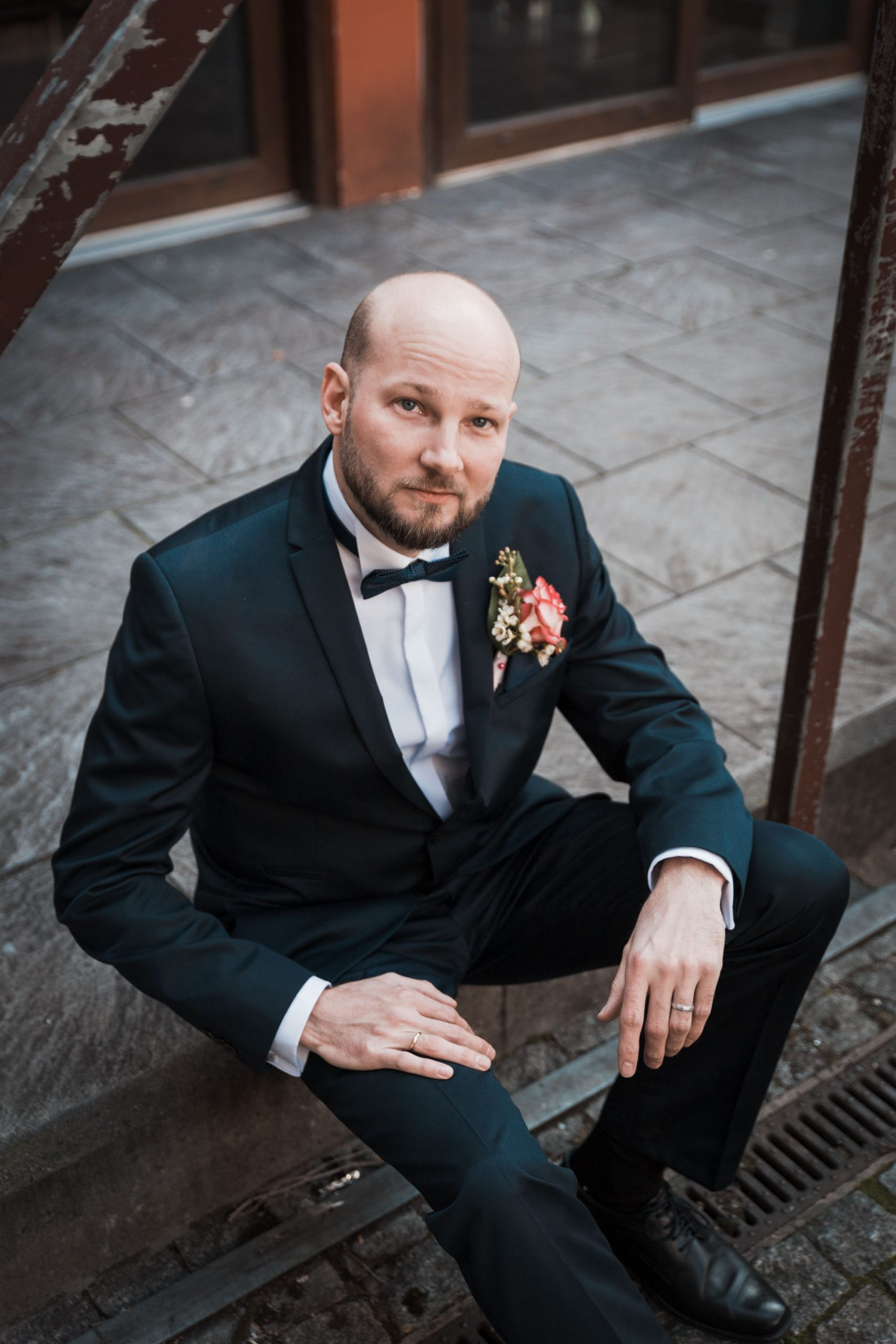 Hochzeitsbild spontan entstanden. Bräutigam sitzt in einem Innenhof der Kölner Altstadt. Natürliches Hochzeitsfoto einer Bräutigam fotografiert vom Hochzeitsfotografen Pixeldreams
