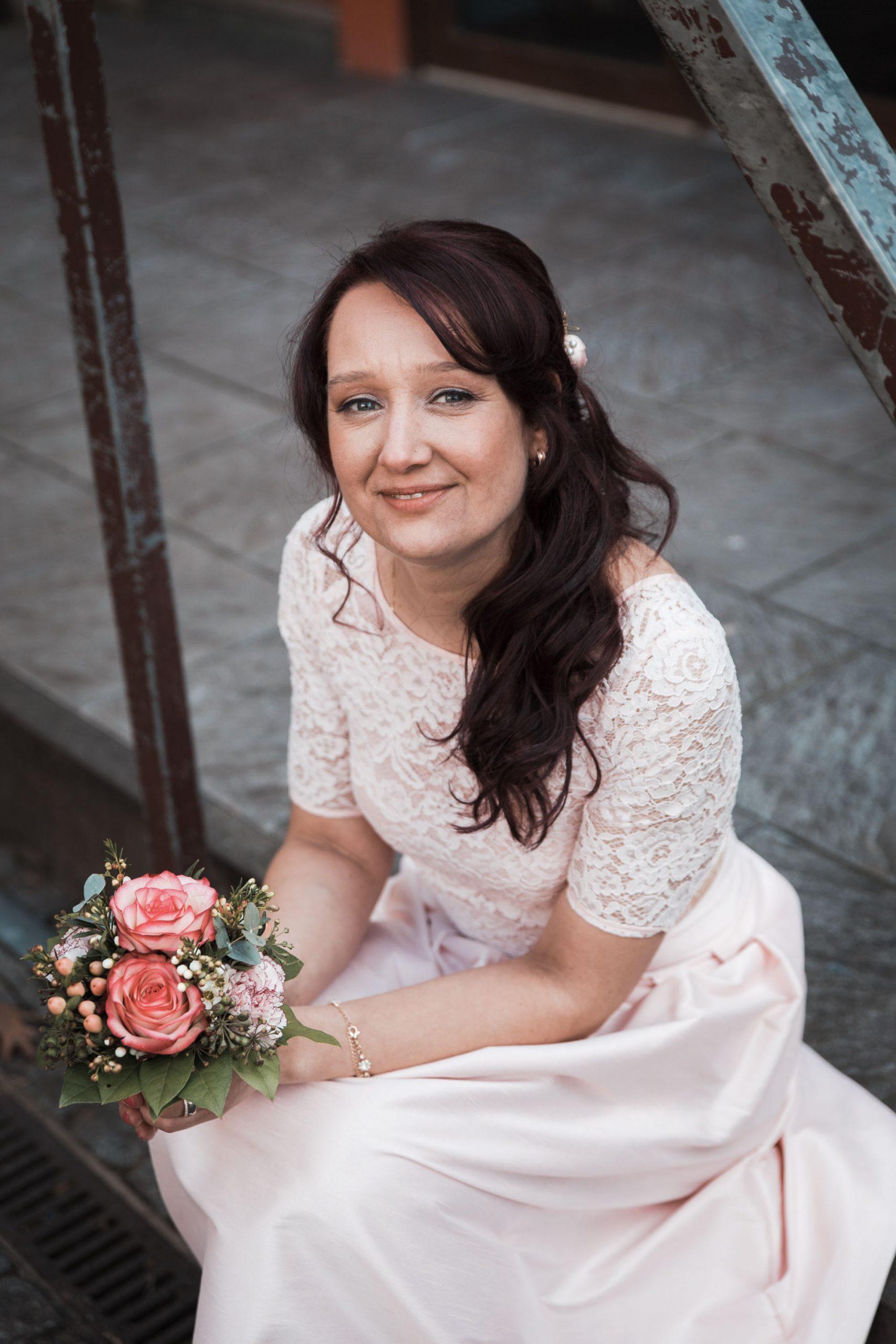 Hochzeitsbild spontan entstanden. Braut sitzt in einem Innenhof der Kölner Altstadt. Natürliches Hochzeitsfoto einer Braut fotografiert vom Hochzeitsfotografen Pixeldreams