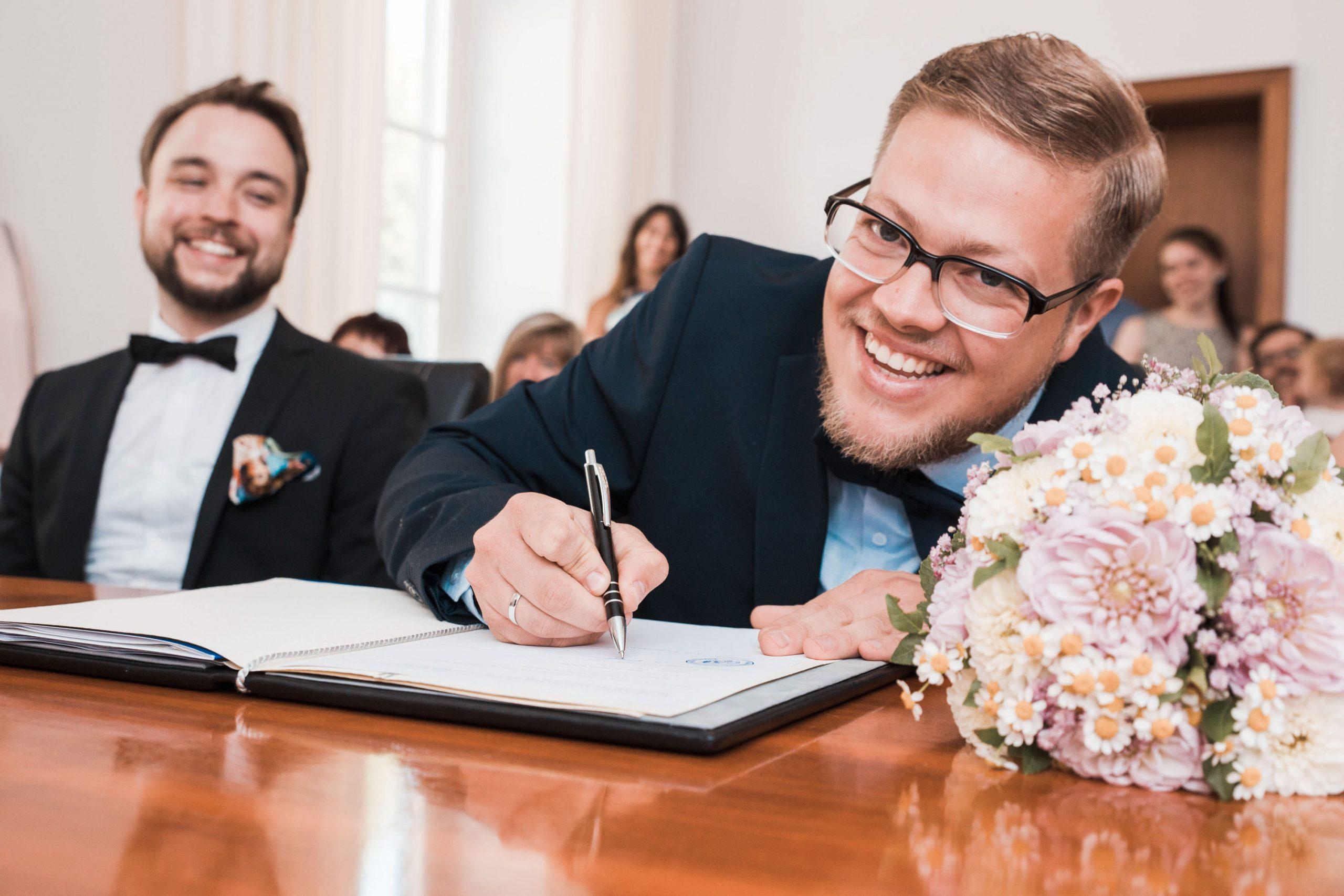 Hochzeitsfoto vom Bräutigam während der standesamtlichen Zeremonie. Bräutigam unterschreibt seine Heiratsurkunde Und Blick glücklich in die Kamera. Kreatives Hochzeitsbild eines professionellen Hochzeitsfotografen.