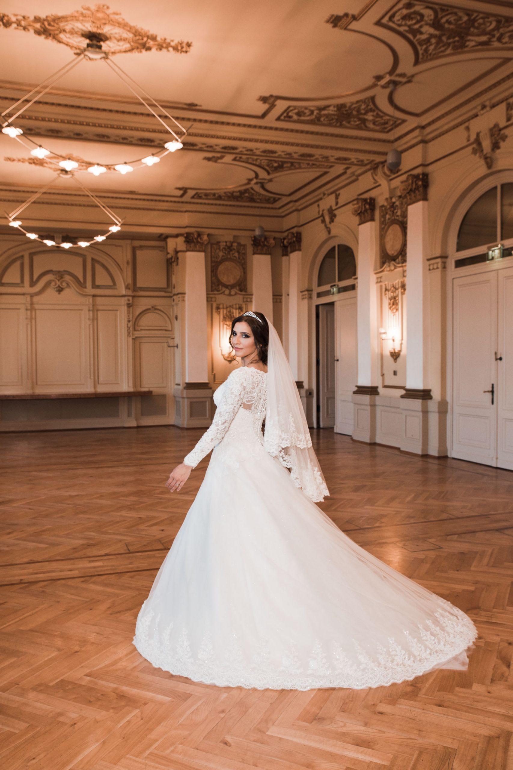 Hochzeitsfoto entstanden in der Stadthalle Wuppertal. Wundervolle Location mit viel Stuck, Schmuck und edler Einrichtung. Braut präsentiert ihr Brautkleid von hinten. Kreatives Hochzeitsfoto vom Hochzeitsfotografen Pixeldreams.