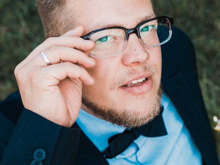 Hochzeitsbild vom Bräutigam aus erhöhter Perspektive. Bräutigam richtet seine Brille und schaut dabei in die Kamera. Kreatives Hochzeitsfoto mit Ringlicht im Einsatz.