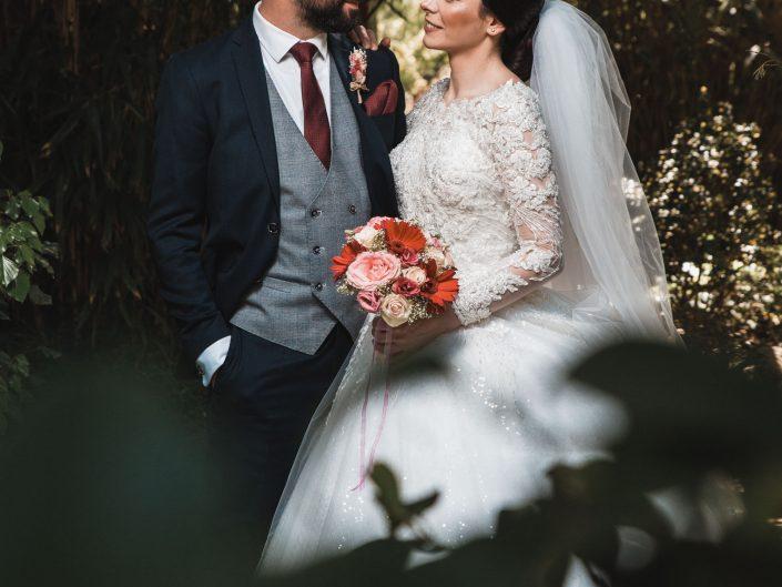 Hochzeitsfoto eines Brautpaares im japanischen Garten in Leverkusen. Hochzeitsfotograf steht hinter Ästen und beobachtet das Paar aus einer Voyeur-Perspektive. Kreatives Hochzeitsfoto.