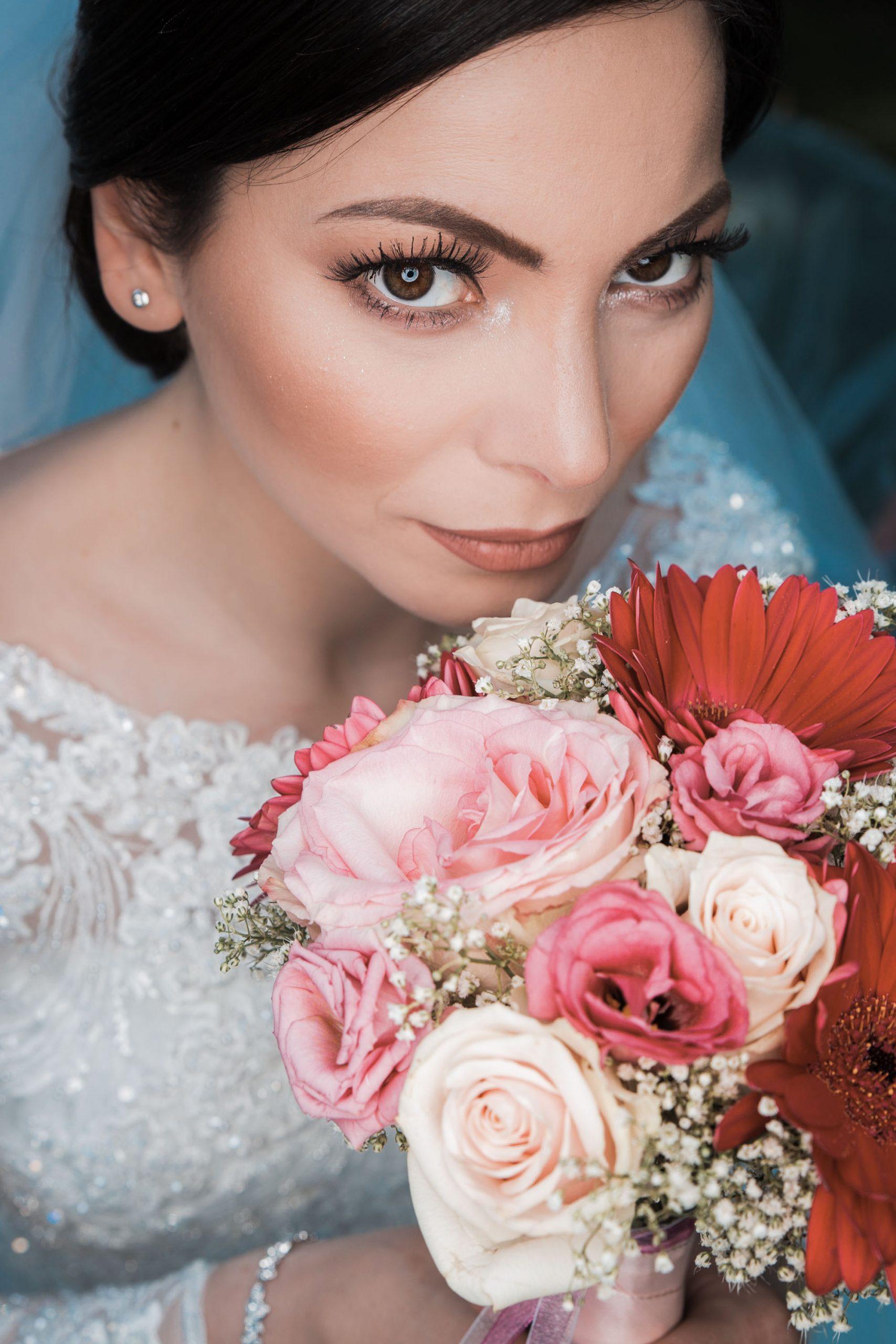 Hochzeitsbild einer Braut mit Braut Strauß in der Hand. Sie schaut von unten nach oben in die Kamera. Ring Licht kam als Beleuchtung zum Einsatz. Ein wunderschönes und kreatives Hochzeitsfoto.