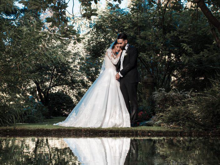 Hochzeitsbild eines türkischen Brautpaares am Wasser im japanischen Garten Leverkusen. Brautpaar spiegelt sich im Wasser. kreatives Hochzeitsfoto.