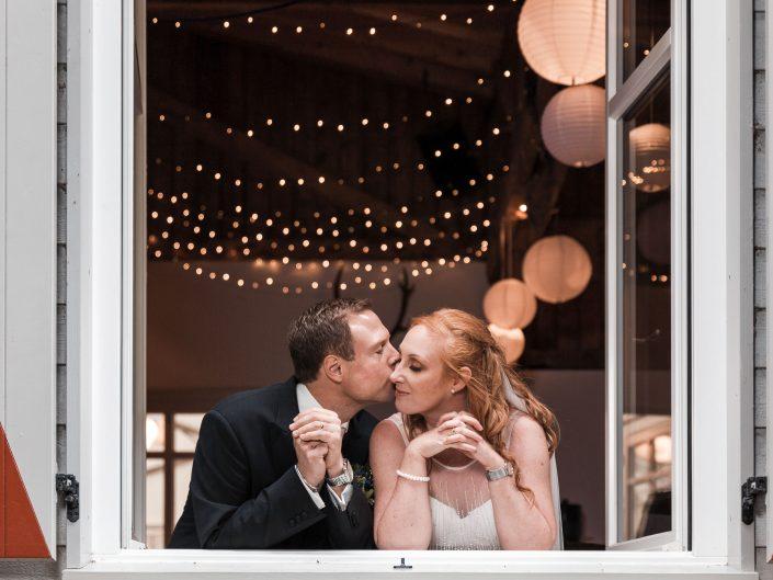 Hochzeitsbild eines Brautpaares. Das Hochzeitspaar Lehnt sich am Fenster der Hochzeitslocation an und posiert für den Hochzeitsfotograf.