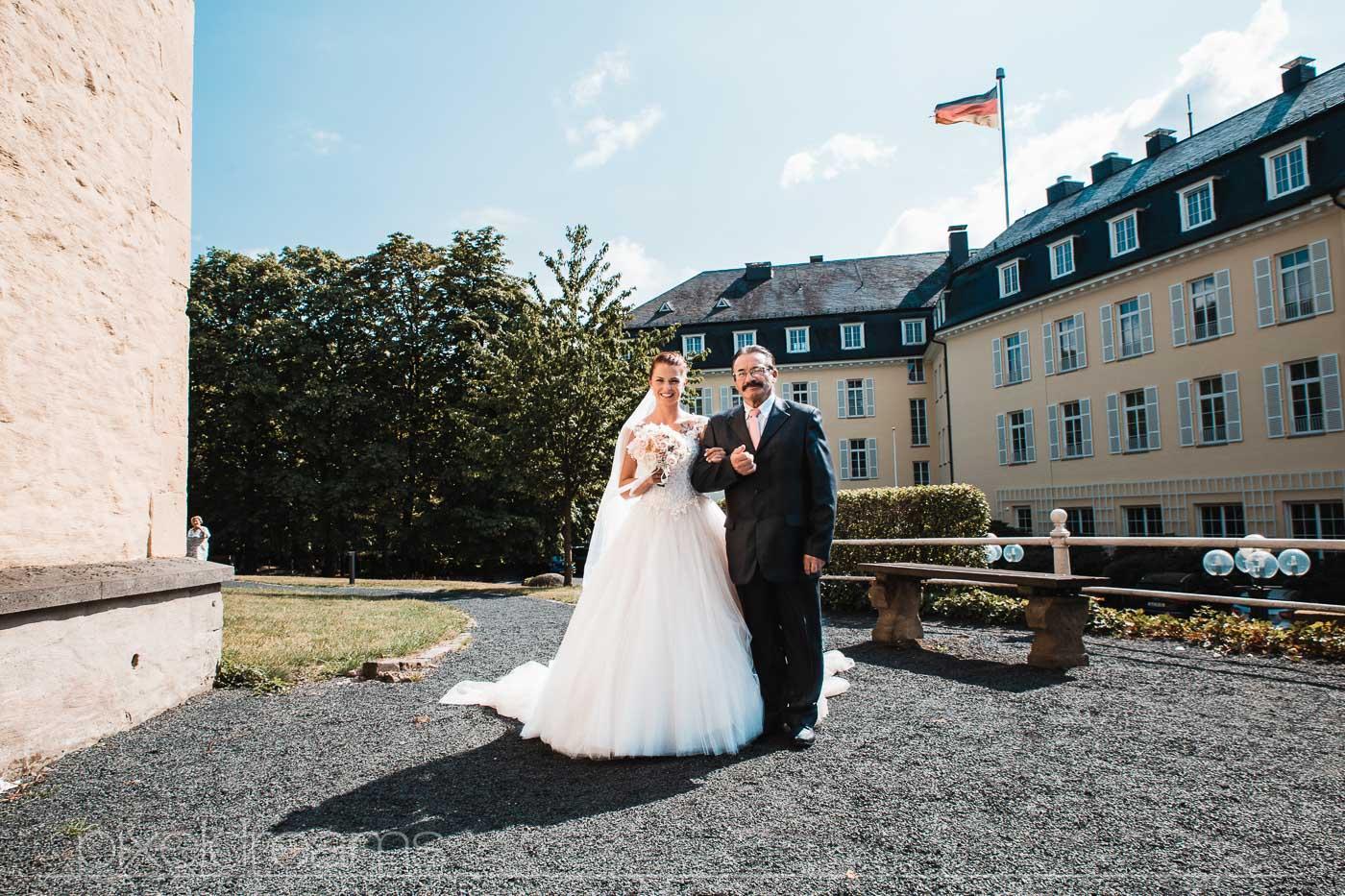 Kurz vor der Trauung vor der Petersberg-Kapelle. Brautvater wartet mit Braut kurz vor dem eintritt in die Kapelle. Hochzeitsfotograf hält diese Situation fest.